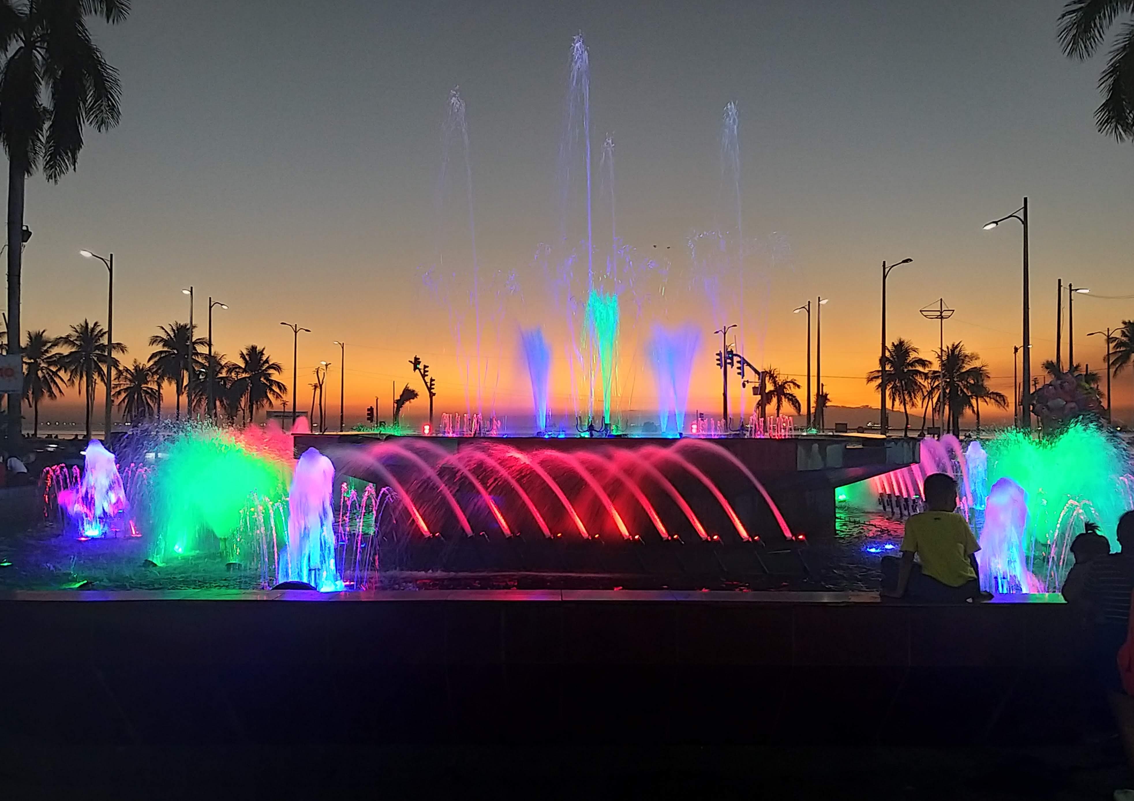 beleuchteter springbrunnen am manila baywalk bei sonnenuntergang