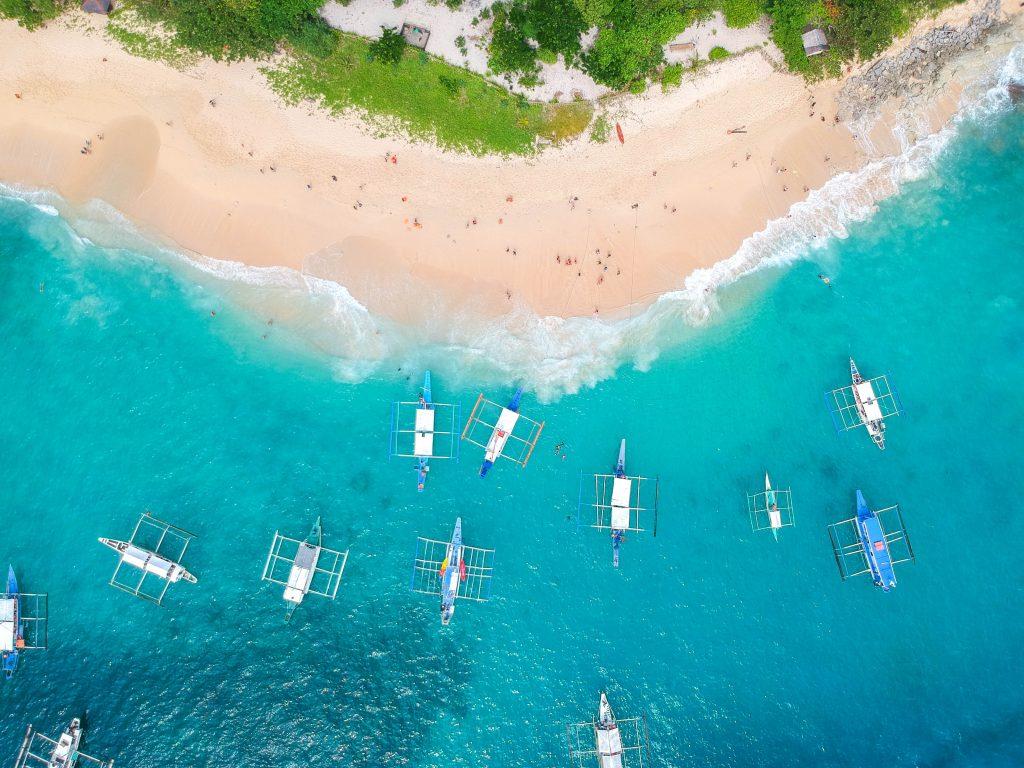 luftaufnahme von türkisem meer mit banca booten und rosaweißem sandstrand